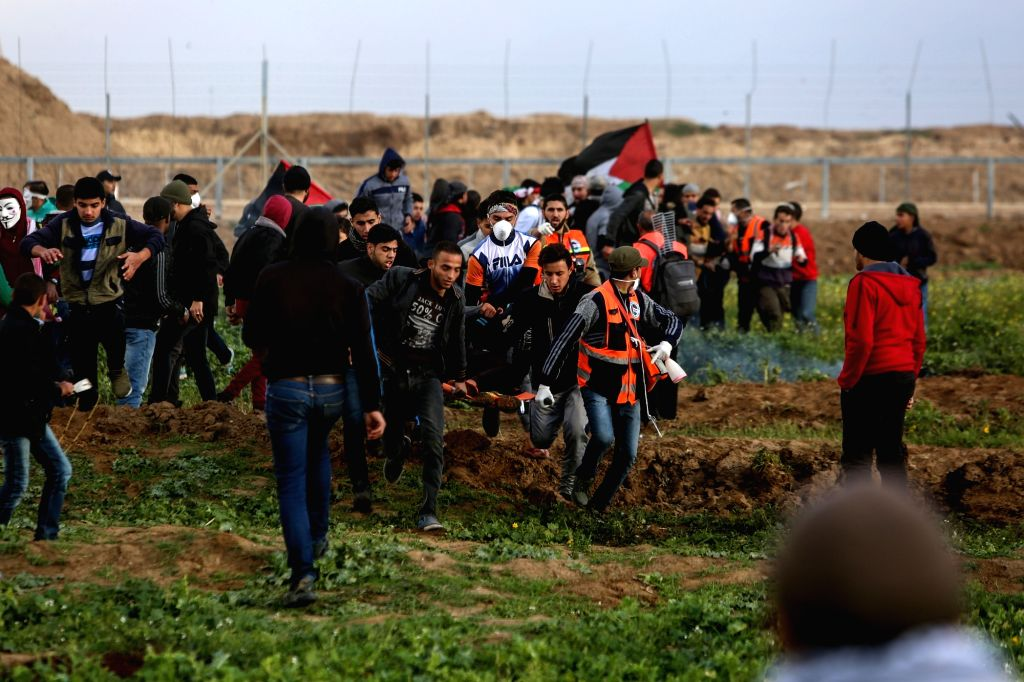 GAZA, March 1, 2019 - Palestinian medics carry a wounded man during clashes with Israeli troops on the Gaza-Israel border, east of Gaza City, on March 1, 2019. Dozens of Palestinian demonstrators ...