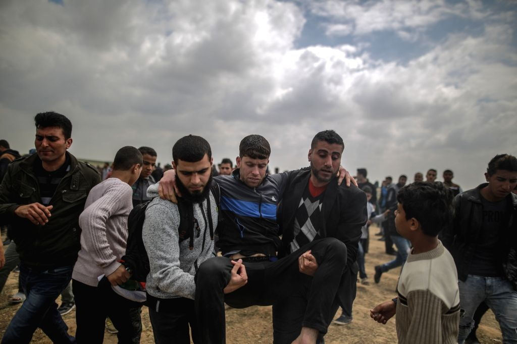 GAZA, March 30, 2018 - A wounded Palestinian is evacuated during a protest along the border fence between Gaza Strip and Israel in Gaza City, March 30, 2018. Although the anti-Israel Palestinian mass ...