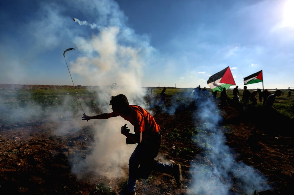 GAZA, March 8, 2019 - A Palestinian protester uses a slingshot to hurl stones at Israeli troops during clashes on the Gaza-Israel border, east of Gaza City, March 8, 2019. One Palestinian was killed ...