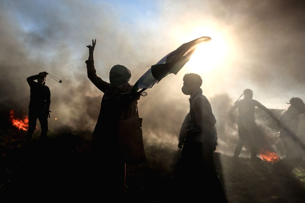 GAZA, March 8, 2019 - A Palestinian woman holds a Palestinian flag during clashes with Israeli troops on the Gaza-Israel border, east of Gaza City, March 8, 2019. One Palestinian was killed and at ...