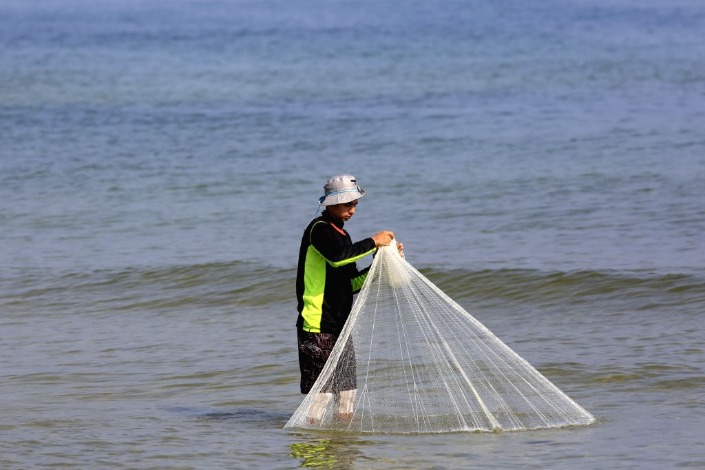 GAZA, May 30, 2019 - Palestinian fisherman Rafat al-Hissi prepares his net on the beach in Gaza City, May 29, 2019. On Wednesday evening, Israel reduced Gaza's fishing area to 10 nautical miles, just ...