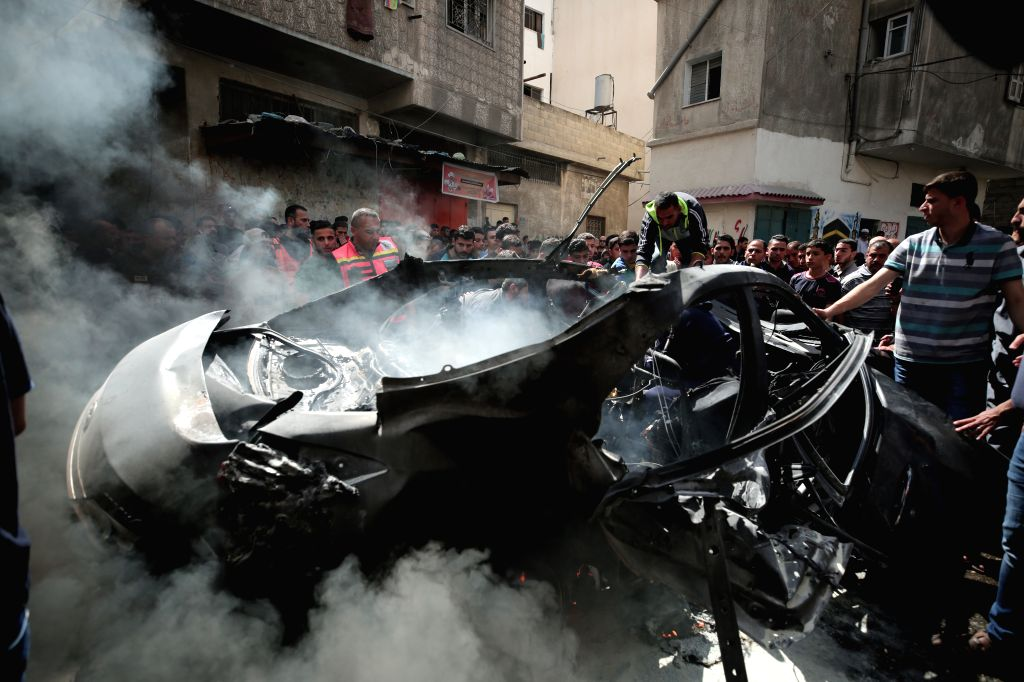 GAZA, May 5, 2019 - Palestinians gather around the wreckage of the car driven by Hammed al-Ghudari, a Hamas commander who was killed in an Israeli airstrike, in Gaza City, May 5, 2019. Gaza Health ...