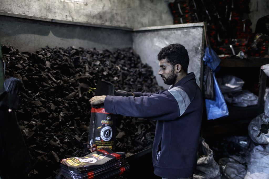GAZA, Nov. 29, 2016 - A Palestinian worker repacks charcoal imported from Egypt into small bags to be sold for 6 Shekels (1.5 USD) in public markets in Gaza City on Nov. 28, 2016. Palestinians ...