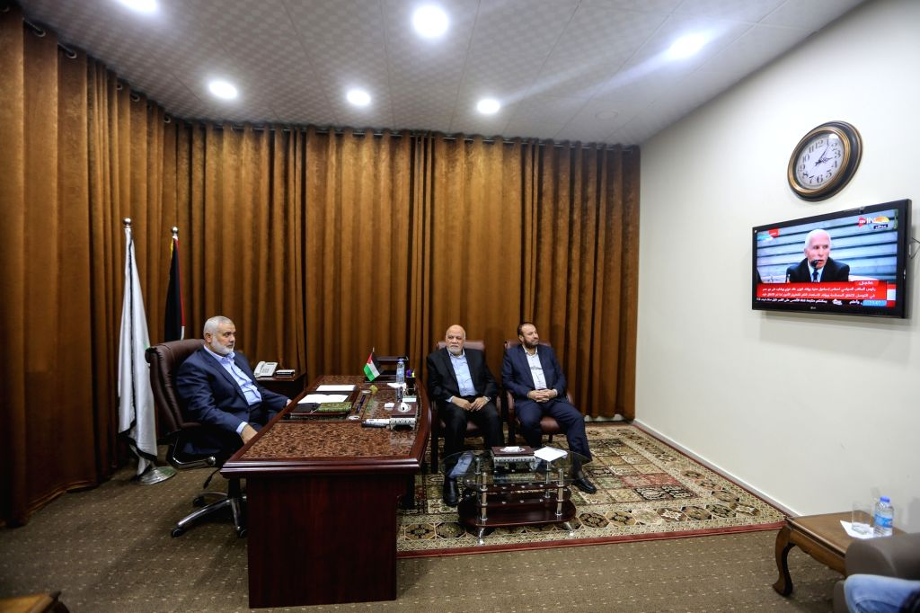 GAZA, Oct. 12, 2017 - Islamic Hamas Movement leader Ismail Haniya (L) watches the coverage of a reconciliation agreement signed by Palestinian rival movements Fatah and Hamas, at his office in Gaza ...