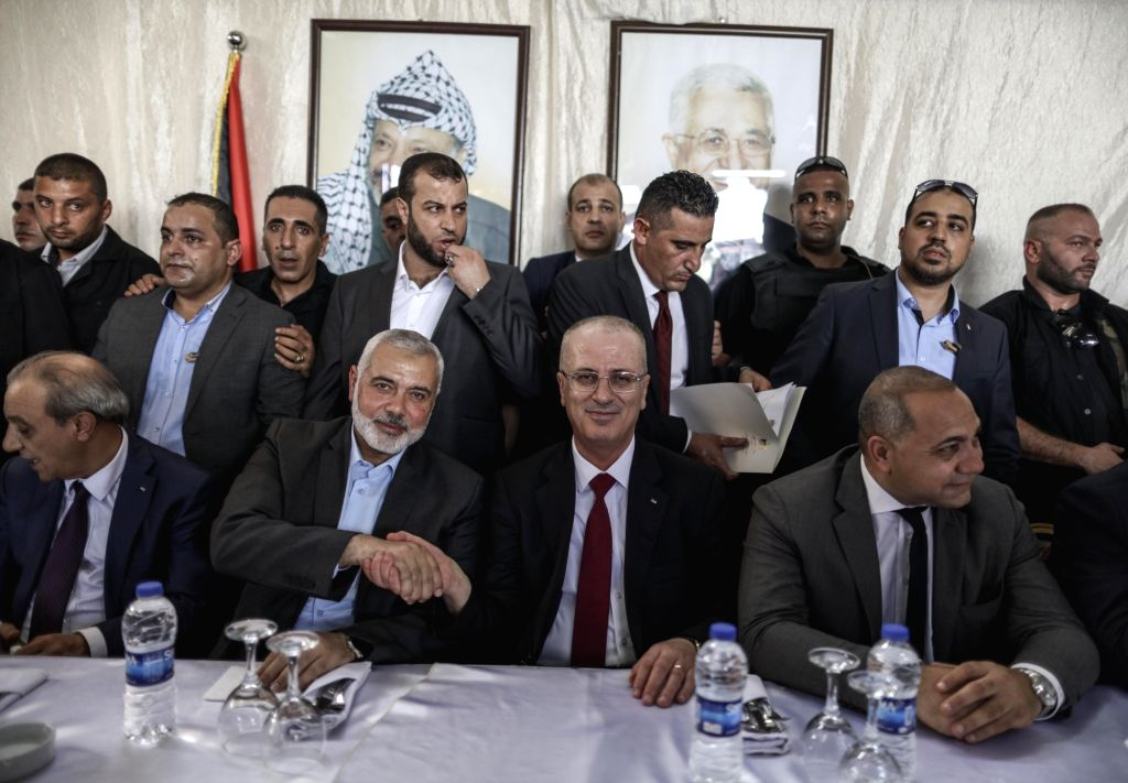 GAZA, Oct. 2, 2017 - Rami Hamdallah (2nd R, front), Prime Minister of the Palestinian Consensus Government, shakes hands with Hamas Chief Ismail Haniyeh (2nd L, front) in Gaza Strip, on Oct. 2, 2017. ...
