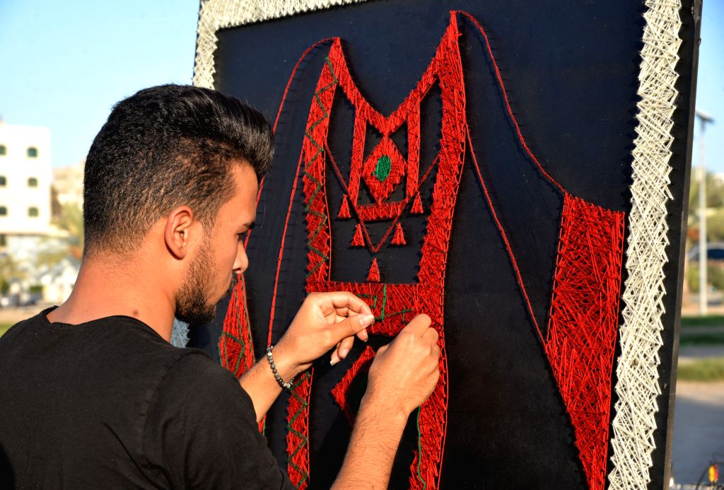 GAZA, Oct. 8, 2019 - A Palestinian artist makes a traditional Palestinian dress during a heritage exhibition as a part of the events to mark the Palestinian Heritage Day at Arts and Crafts Village in ...