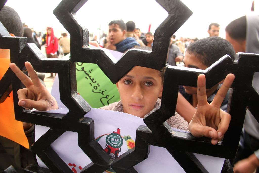 Palestinians take part in a protest calling the Egyptian authorities to open the Rafah border crossing, at the Rafah crossing in the southern Gaza Strip city of Rafah on November 23, 2014. ...