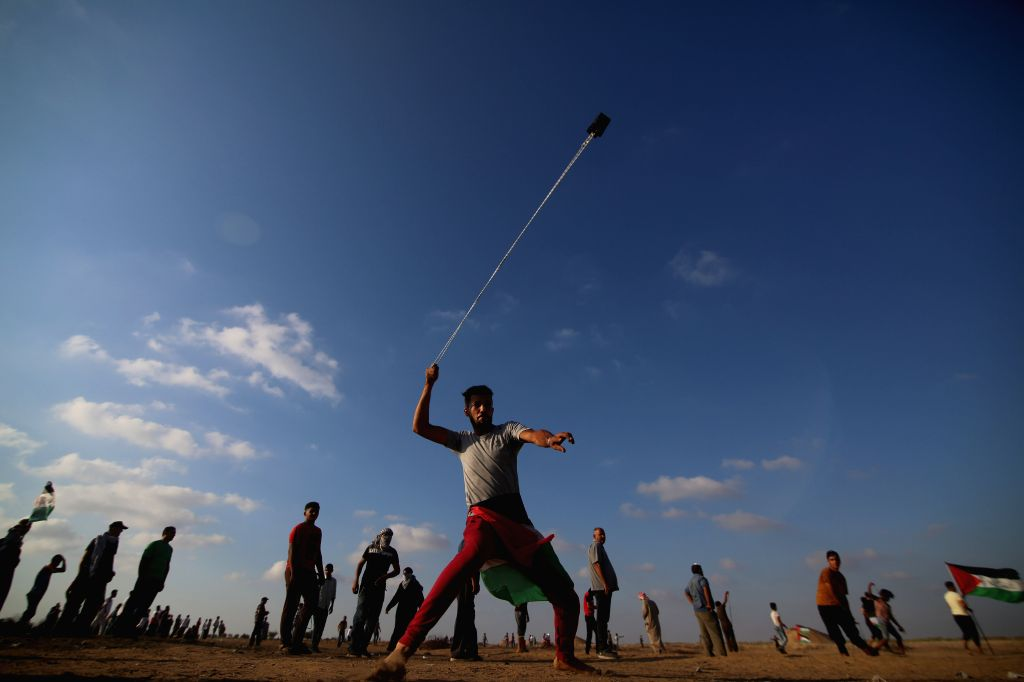 GAZA, Sept. 14, 2019 - A Palestinian protester uses a slingshot to hurl stones at Israeli troops during clashes on the border with Israel, in east of southern Gaza Strip city of Khan Younis, Sept. ...