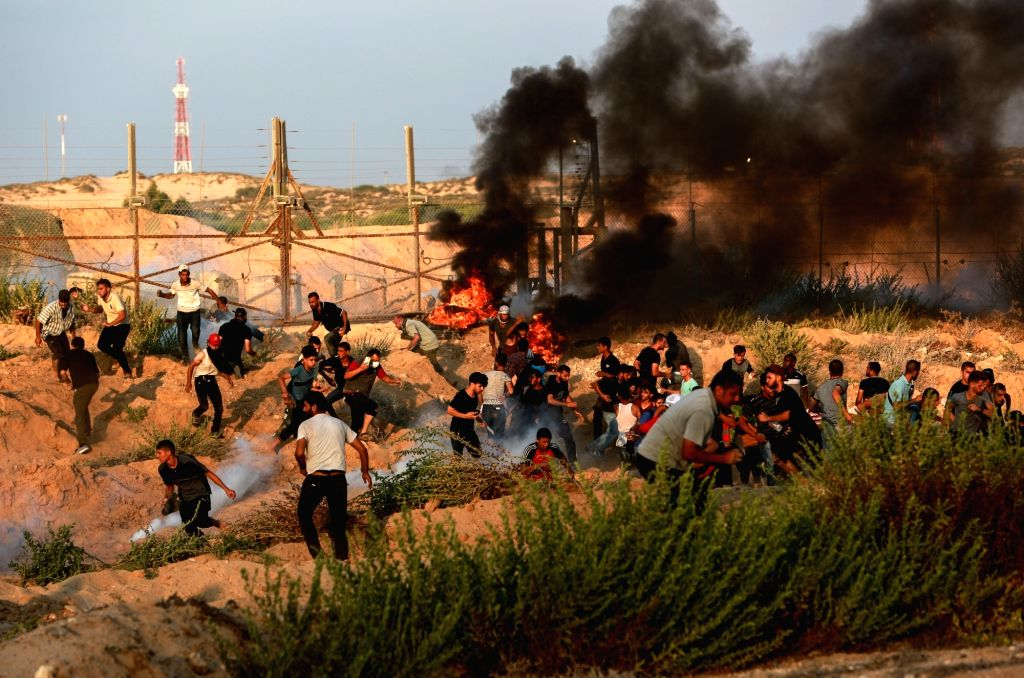 GAZA, Sept. 17, 2018 - Palestinian protesters run to take cover from tear gas canisters fired by Israeli troops during clashes near the border between the northern Gaza Strip and Israel, on Sept. 17, ...