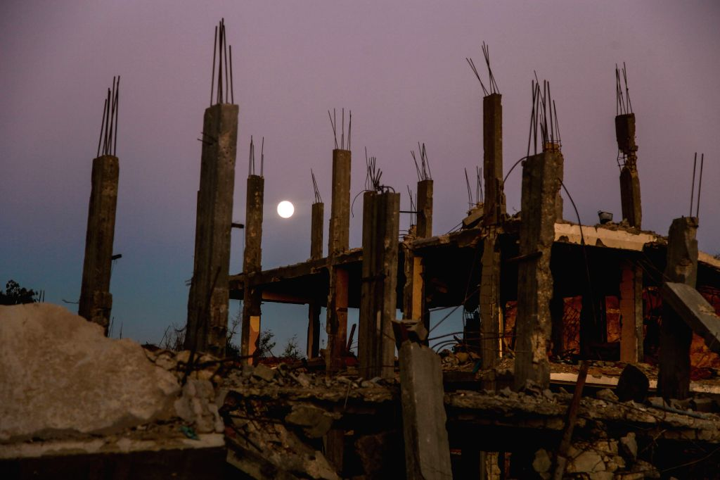 GAZA, Sept. 2014 Rubbles of destroyed houses are seen under a full moon in Gaza City, on Sept 8, 2014.
