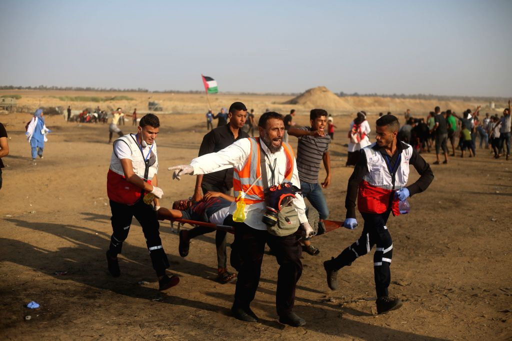 GAZA, Sept. 21, 2019 - Palestinian medics carry a wounded man during clashes on the Gaza-Israel border, east of Gaza City, Sept. 20, 2019. At least 74 Palestinians were injured on Friday during the ...