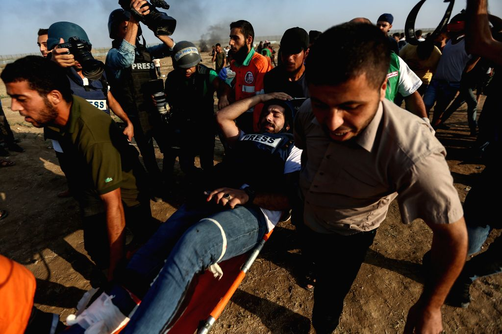 GAZA, Sept. 21, 2019 - Palestinian medics carry a wounded journalist during clashes on the Gaza-Israel border, east of Gaza City, Sept. 20, 2019. At least 74 Palestinians were injured on Friday ...