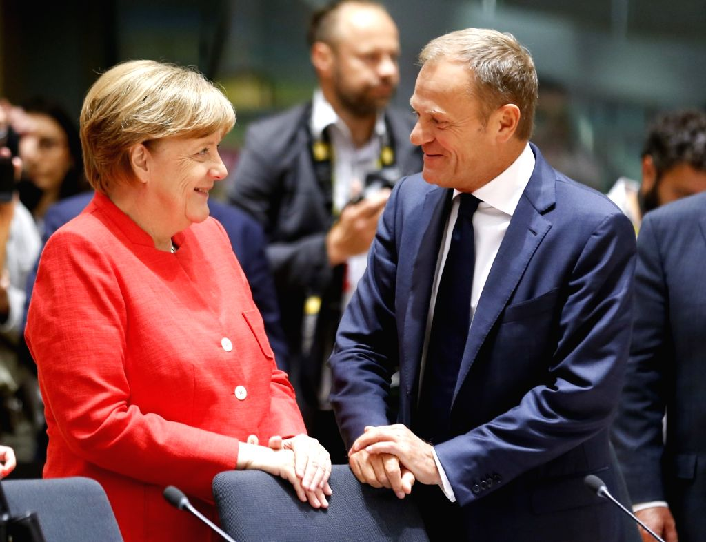 German Chancellor Angela Merkel (L) talks with European Council President Donald Tusk at second day's EU Summit in Brussels, Belgium, June 23, 2017.