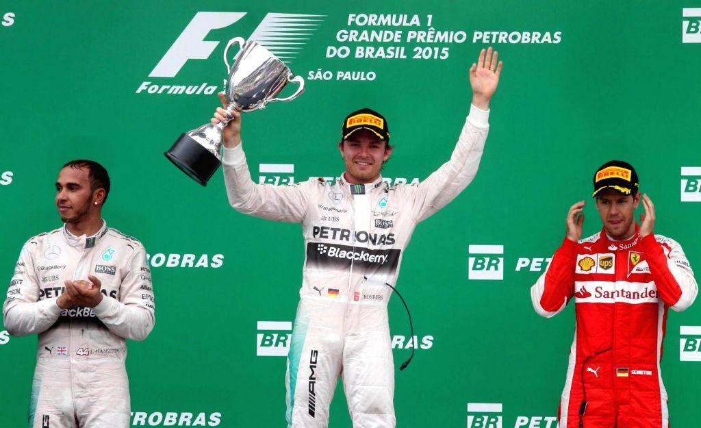 German pilot Nico Rosberg (C), and British Lewis Hamilton (L) of Mercedes team, and German Sebastian Vettel (R) of Ferrari team, celebrate on the podium after the ...