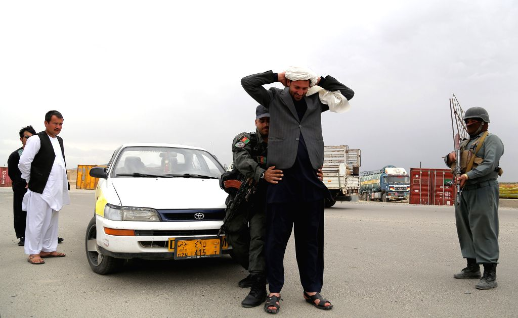 An Afghan policeman searches a passenger at a checkpoint in Ghazni province, Afghanistan, April 11, 2015. A roadside bomb struck a vehicle in Ghazni province on ...