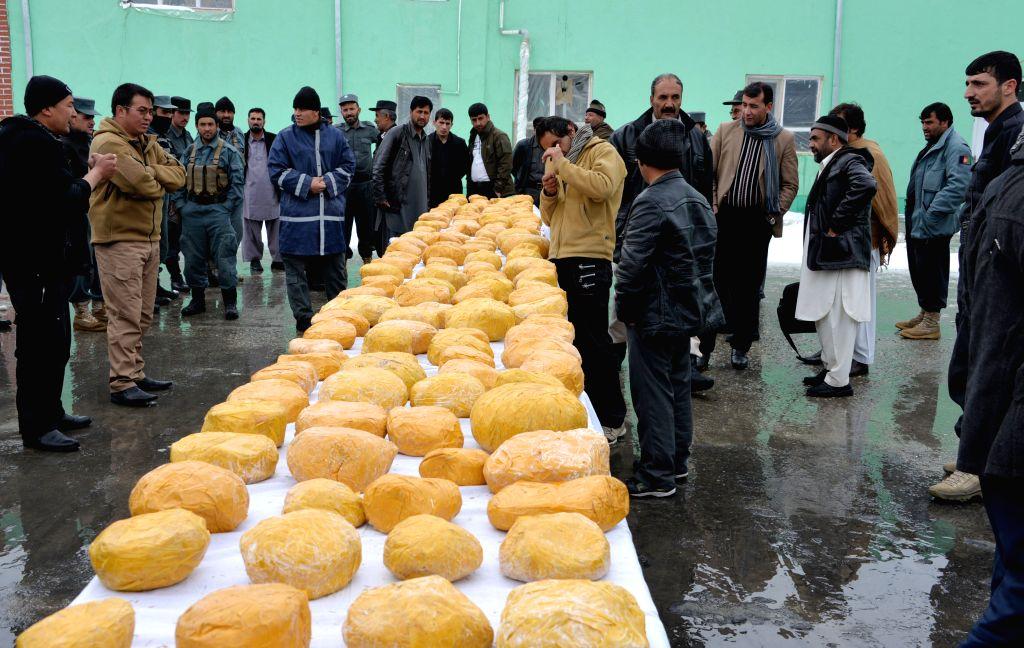 Afghan policemen display drugs after capturing a drug smuggler with 288 kilograms of drugs during an operation in Ghazni province, eastern Afghanistan, Feb. 7, 2015. .