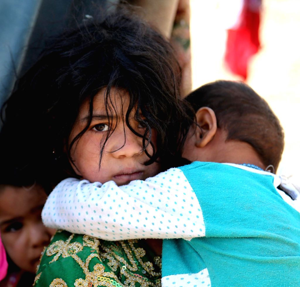 An Afghan girl holds her younger brother at a camp in Ghazni province, eastern Afghanistan, Sept. 3, 2014.
