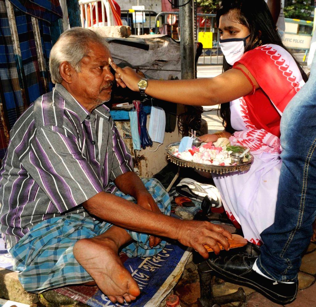 Girls celebrate Bhai Dooj with a cobbler, in Kolkata on Nov 16, 2020.