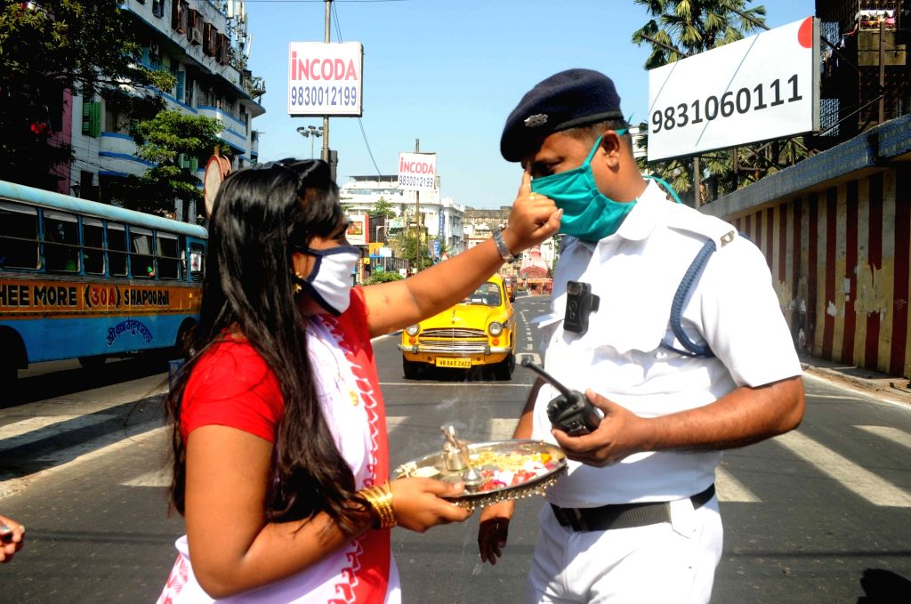 Girls celebrate Bhai Dooj with a traffic policeman, in Kolkata on Nov 16, 2020.