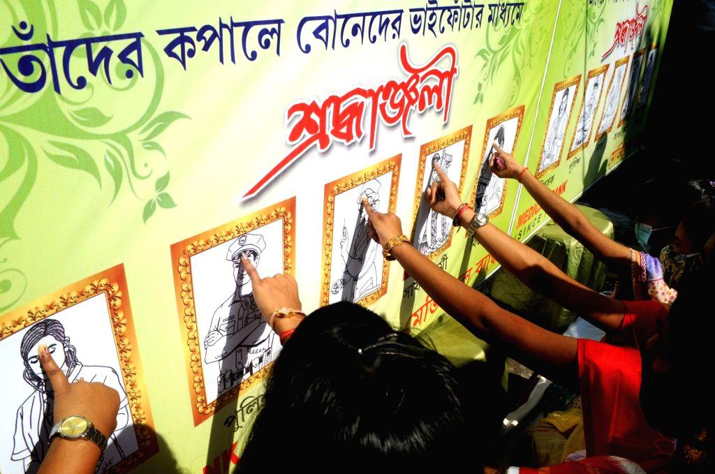 Girls celebrate Bhai Dooj with the poster of COVID-19 warriors, in Kolkata on Nov 16, 2020.