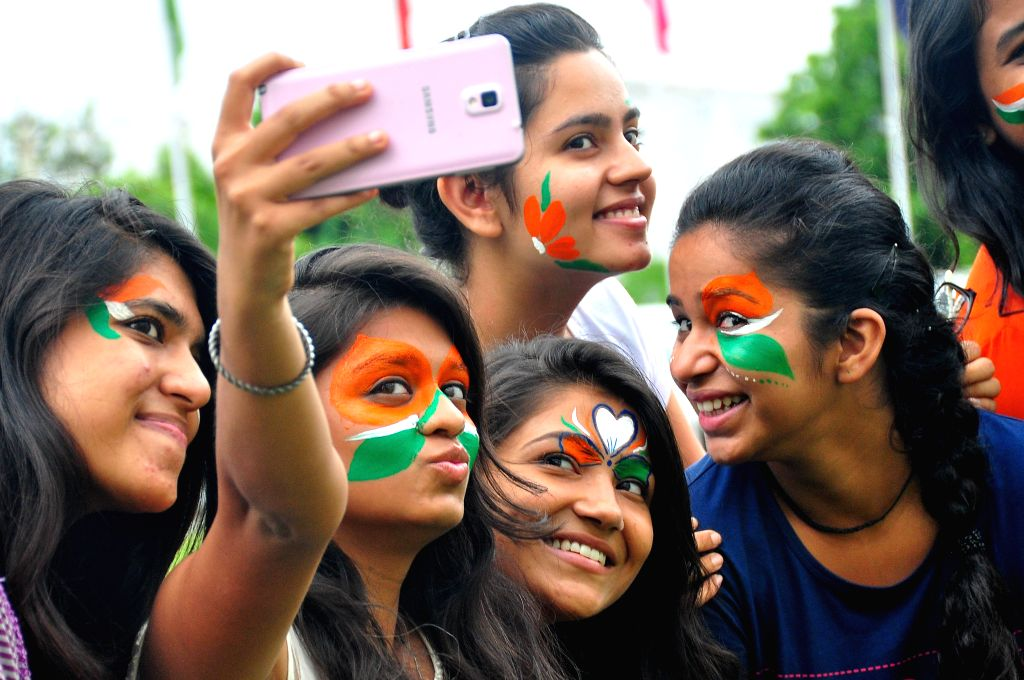 Girls click a selfie with their face painted in tricolors on the eve of Independence Day in Jaipur, on Aug 14, 2015.