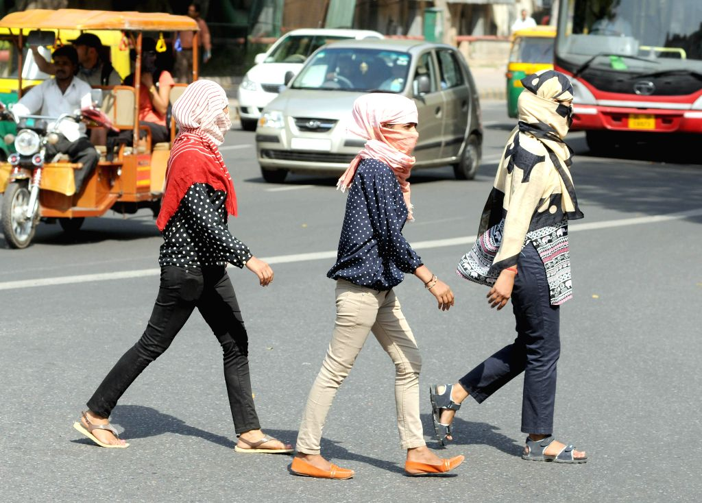 Girls cover their face to protect themselves from direct sun light as mercury touched 38 degrees Celsius in in New Delhi on April 24, 2014.