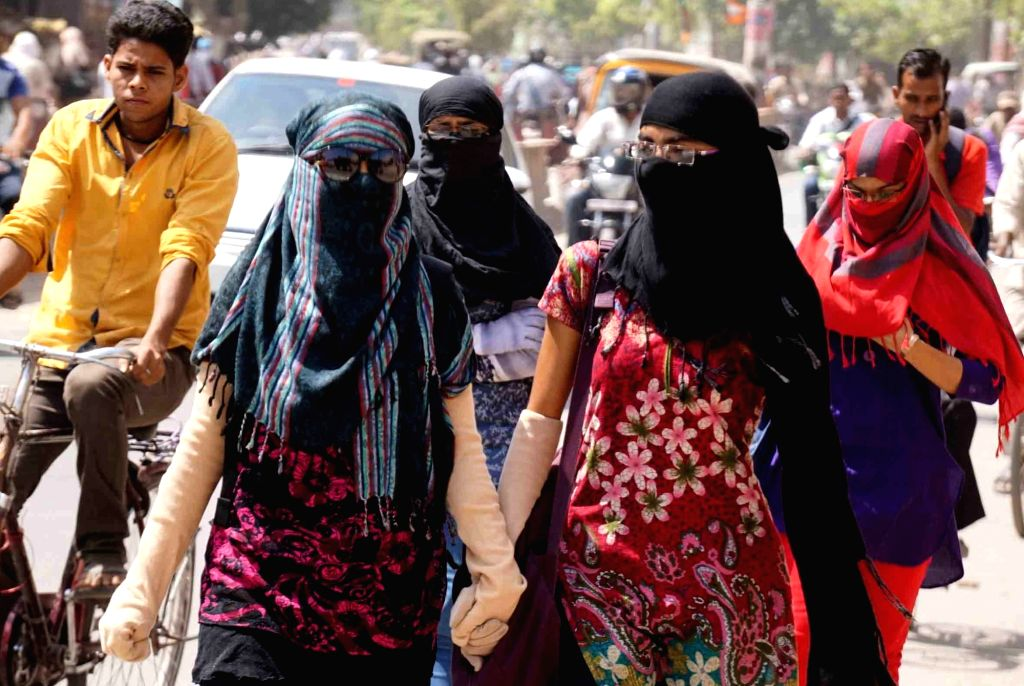 Girls cover their faces to avoid direct sunlight on a hot day in Varanasi on May 16, 2017.