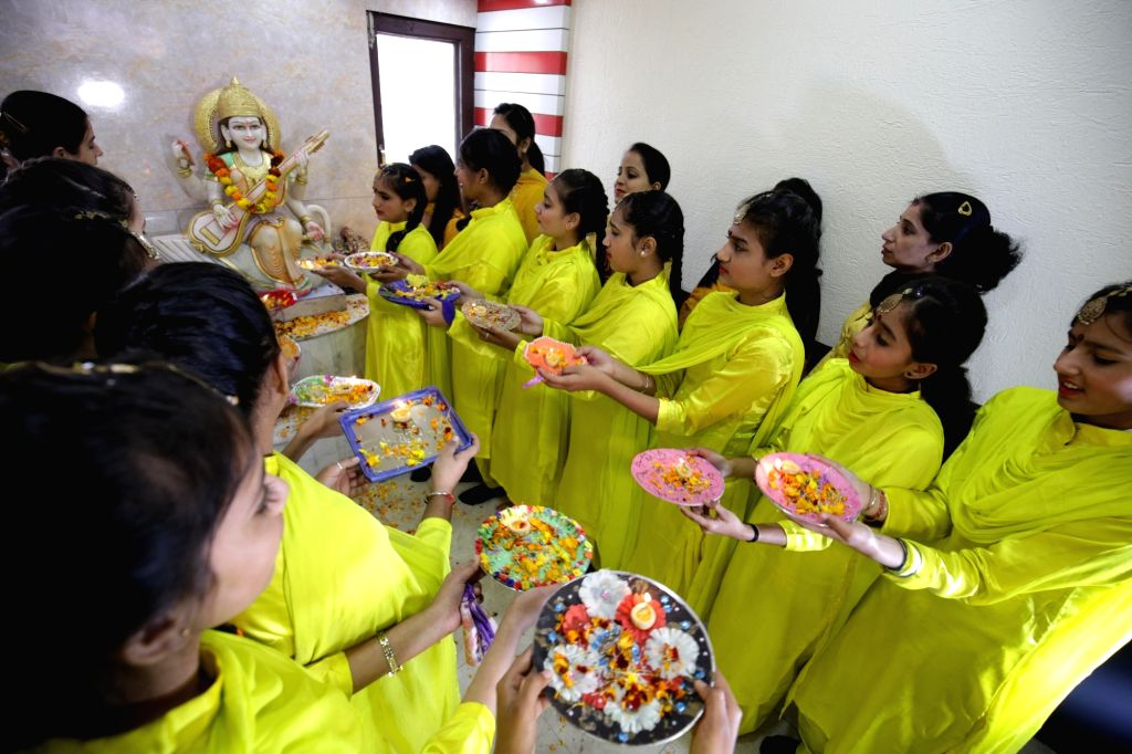 Girls dressed in yellow perform rituals on the eve of Basant Panchami festival in Amritsar, on Feb 9, 2019.