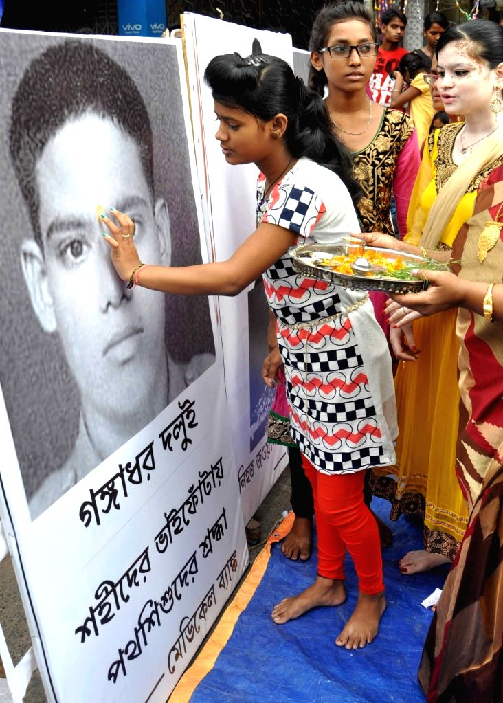 Girls mark the foreheads of martyrs with sandalwood paste on Bhai Phonta in Kolkata, on Nov 1, 2016.