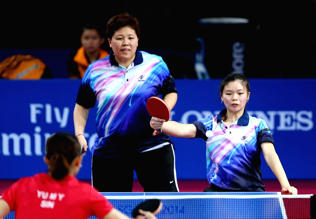 Ho Ying (R)/Beh Lee Wei (C) of Malaysia compete during the women's team final of table tennis against Lin Ye/Yu Mengyu of Singapore at the 2014 Glasgow Commonwealth