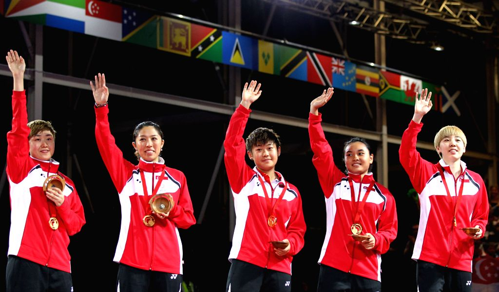 Players of Singapore celebrate their victory on the podium during the awarding ceremony for the women's team final of table tennis at the 2014 Glasgow Commonwealth .