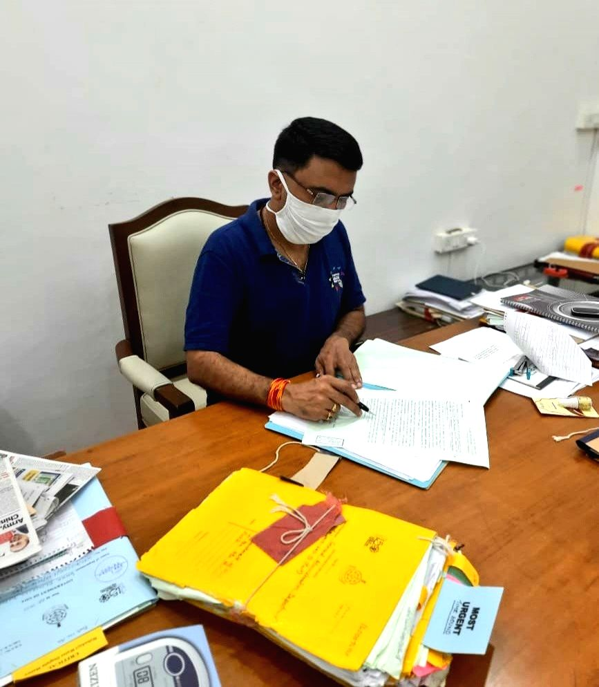 Goa Chief Minister Pramod Sawant who is in home isolation after testing positive for COVID-19, inspecting files at his residence. - Pramod Sawant