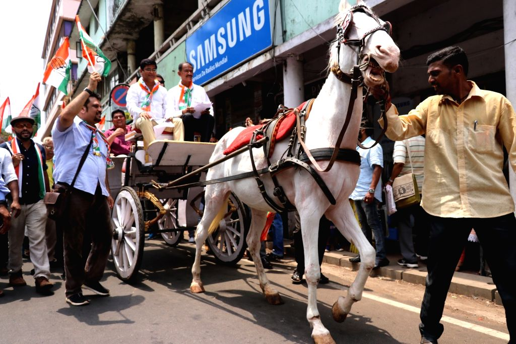 Goa Congress president Girish Chodankar (R) rides a horse-driven tonga as he drives to the North Goa Collectorate to protest against the rising fuel prices, in Panaji on May 24, 2018.