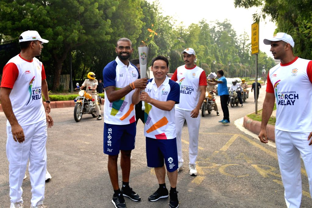 Goalkeepers in the 18-member Indian Men's Hockey Team, P.R. Sreejesh and Krishan B Pathak hold the torch of the 18th Asian Games Jakarta-Palembang 2018 as the torch relay commenced from ... - Krishan B Pathak