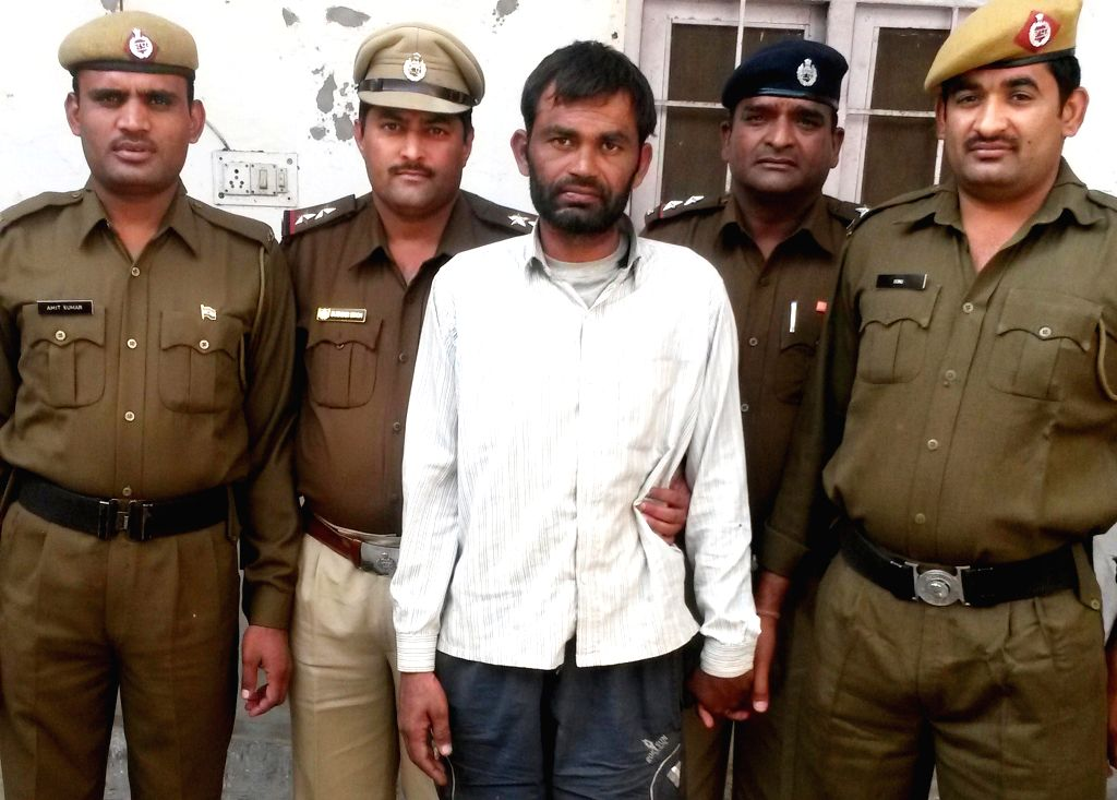 Police personnel present a suspect in connection with a daring bank locker heist in Gohana on Nov 21, 2014. Burglars last month had dug a 125-feet-long tunnel from an adjoining building and ..