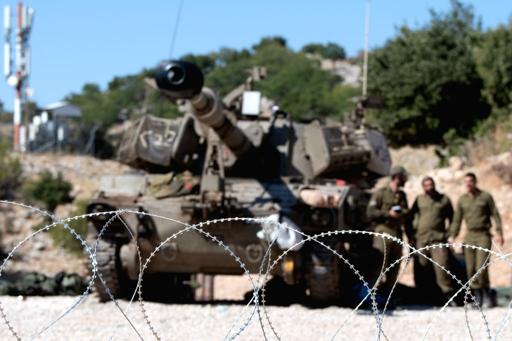 GOLAN HEIGHTS, Aug. 25, 2019 - Israeli soldiers stand next to an armored fighting vehicle in the Israeli occupied Golan Heights, on Aug. 25, 2019. Chief of General Staff of the Israel Defense Forces ...