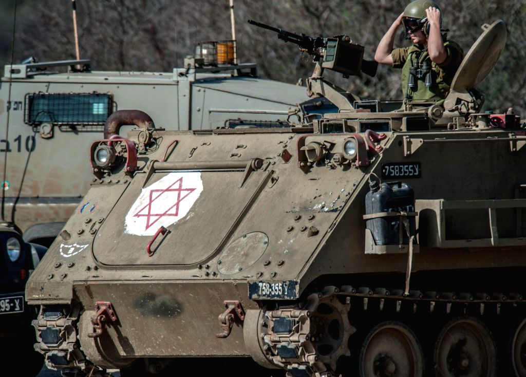 An Israeli soldier stands on the  top of an armoured personnel carrier (APC) after an anti-tank missile hit an Israeli army vehicle near the Israel-Lebanon ...