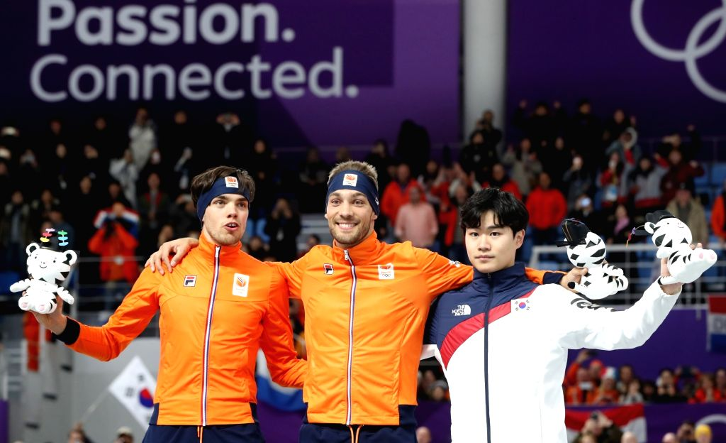 Gold medalist Kjeld Nuis of the Netherlands (C), his compatriot silver medalist Patrick Roest (L), and South Korea's Kim Min-seok pose during the flower ceremony of the men's 1,500 meter ...