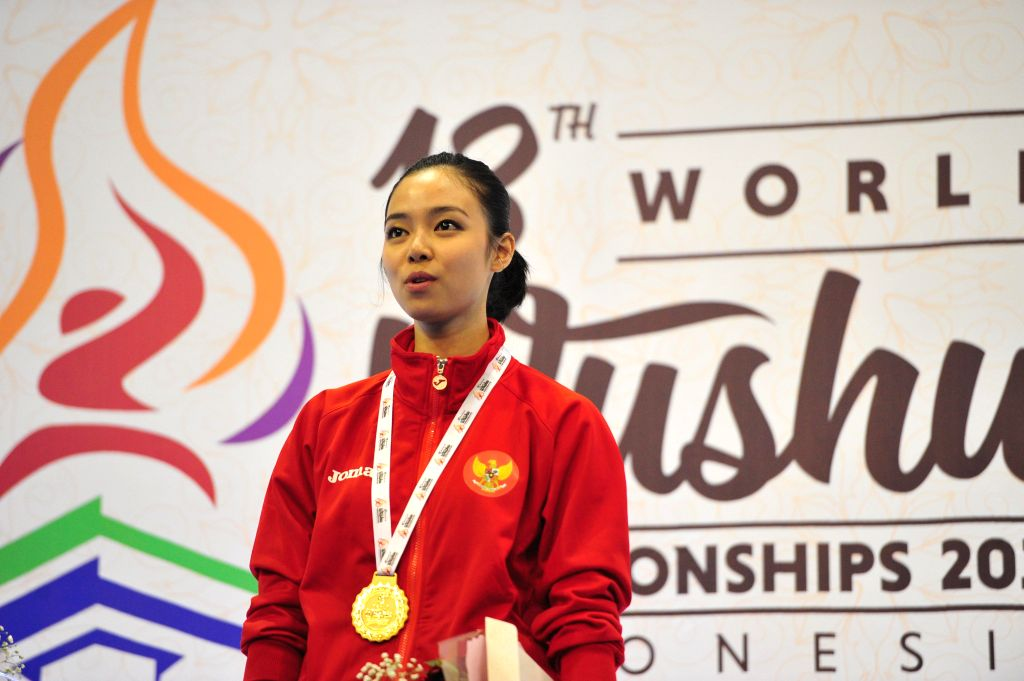 Gold medalist Lindswell of Indonesia poses on the podium during the awarding ceremony of Women's Taijicuan at the 13th World Wushu Championship 2015 in Jakarta, ...