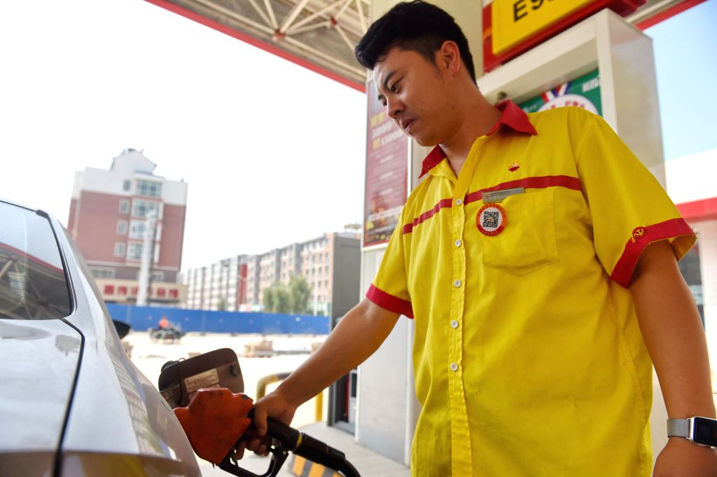 GONGZHULING, Aug. 4, 2016 - A staff member fills a car at a gas station in Gongzhuling City, northeast China's Jilin Province, Aug. 4, 2016. The National Development and Reform Commission (NDRC), ...