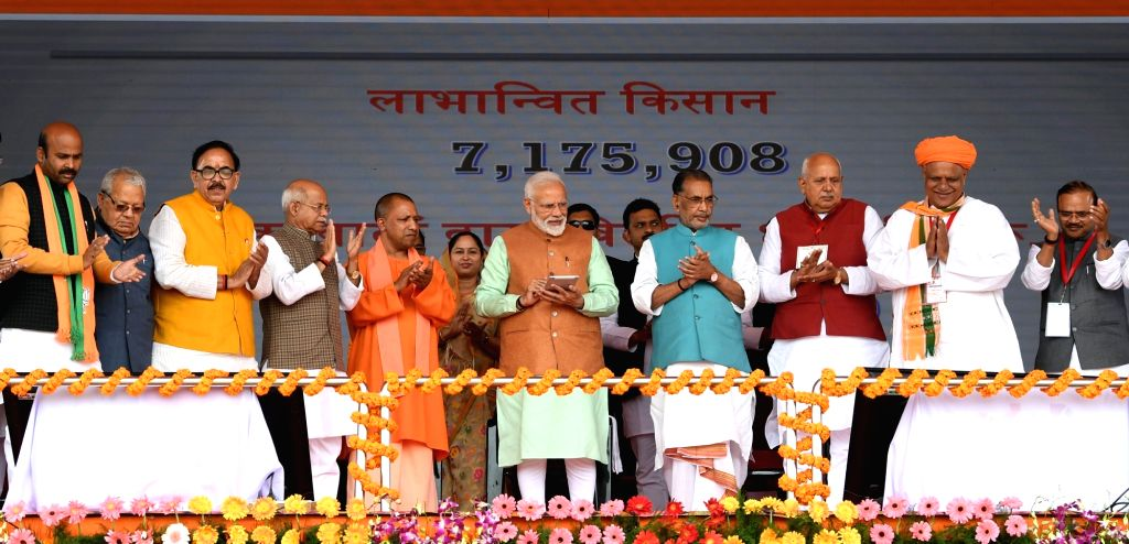 Gorakhpur: Prime Minister Narendra Modi launches Pradhan Mantri Kisan Samman Nidhi (PM-KISAN) scheme in Uttar Pradesh's Gorakhpur, on Feb 24, 2019. Also seen Union Agriculture and Farmers Welfare Minister Radha Mohan Singh, Uttar Pradesh Chief Minist - Narendra Modi and Radha Mohan Singh