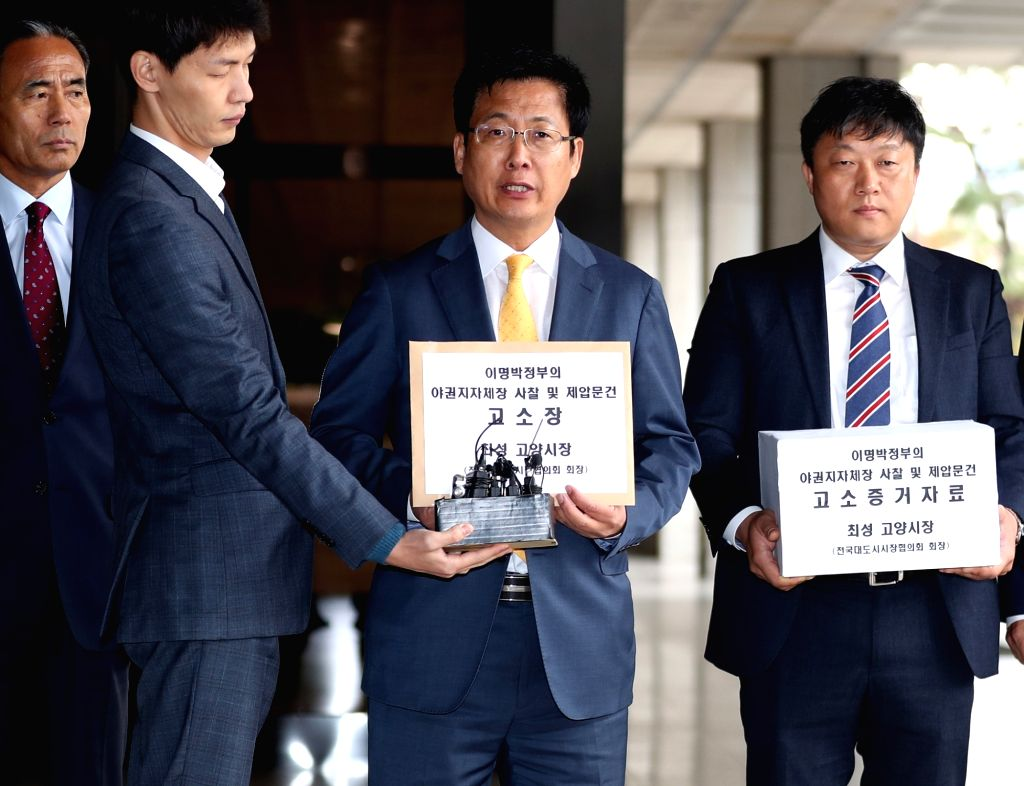 Goyang Mayor Choi Sung (2nd from R) arrives at a prosecution office in Seoul on Oct. 12, 2017, to file a lawsuit against former President Lee Myung-bak and his spy chief Won Sei-hoon for their ...