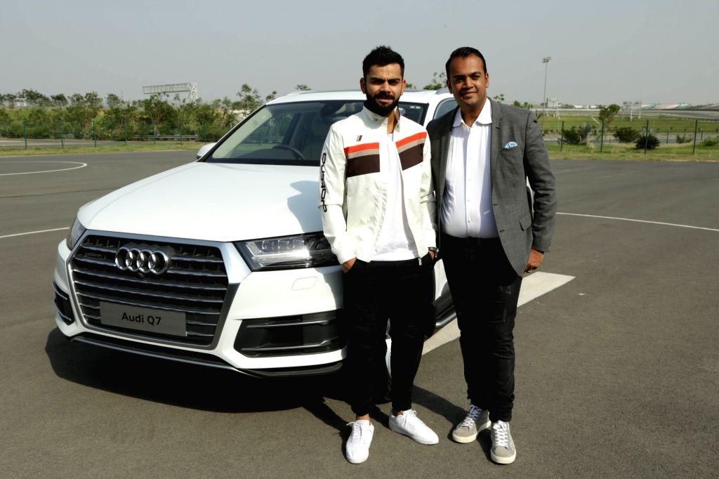 Greater Noida: Audi India Head Rahil Ansari presents keys of Audi Q7 45 TDI to Indian cricketer Virat Kohli at Buddh International Circuit in Greater Noida on May 11, 2017. - Virat Kohli