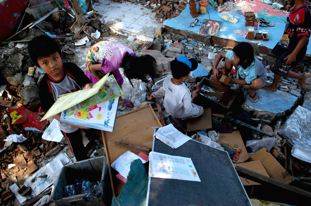 GRESIK, June 3, 2016 - Children collect books and equipment among the ruins of the Kusuma Kindergarten in Gresik, East Java, Indonesia, June 3, 2016. The building collapsed after storms and heavy ...