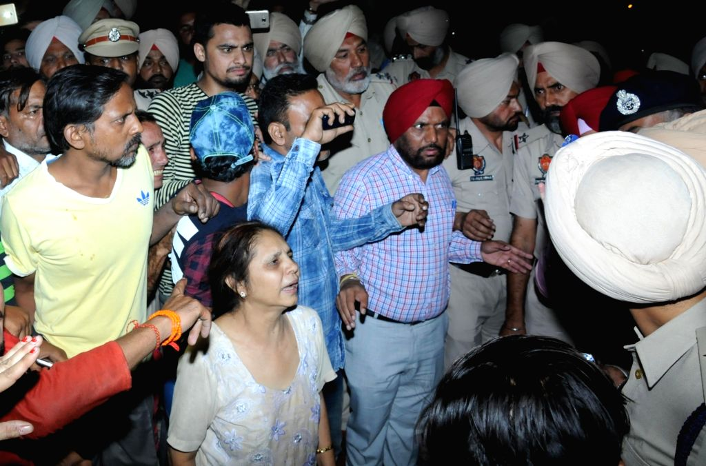 Grief struck relatives of those who were mowed down by a speeding train while watching Ravan Dahan standing on railway tracks in Amritsar on Oct 19, 2018. At least 30 people were killed.