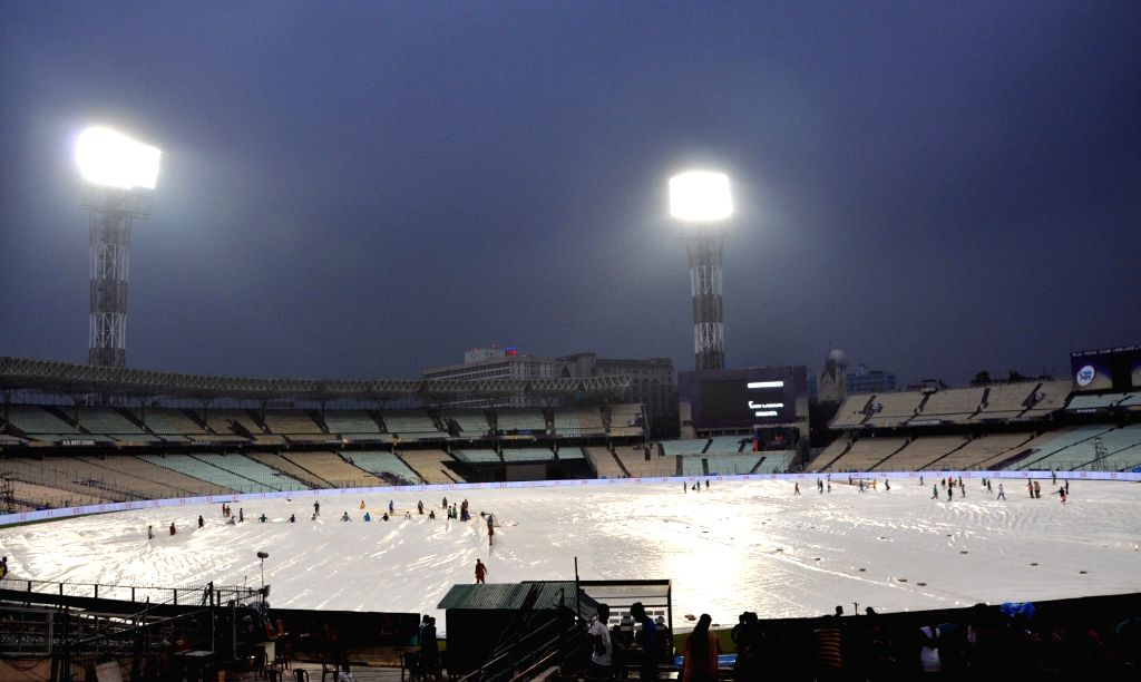 Ground staff busy covering the Eden Gardens ground with plastic sheets during rains, in Kolkata on April 7, 2018.