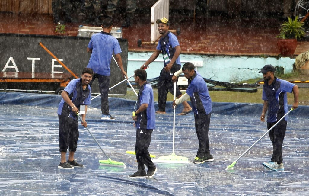 Ground staff clearing water from the plastic sheets during rains ahead of the first T20I match between India and South Africa in Dharamsala on Sep 15, 2019.