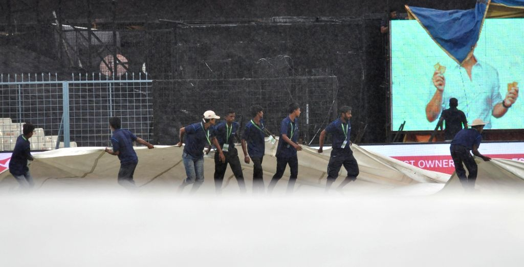 Groundsmen cover the ground with tarpaulin sheets due to the rains during the second ODI cricket match between India and Australia at Eden Gardens in Kolkata on Sept 21, 2017.