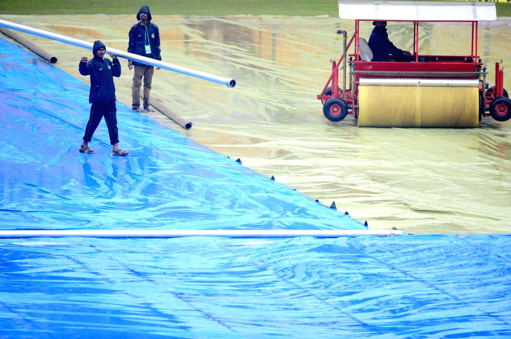 Groundsmen cover the pitch with tarpaulin sheets as rain delay the start of the 2nd day of the second test match between India and South Africa at M Chinnaswamy Stadium in Bengaluru, on ...