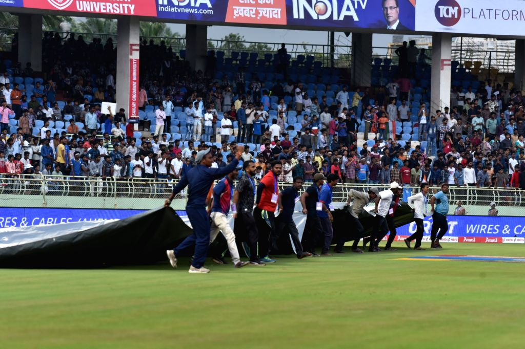 Groundsmen cover the pitch with tarpaulin sheets as rain stops the Day 1 of the 1st Test match between India and South Africa at Dr. Y.S. Rajasekhara Reddy ACA-VDCA Cricket Stadium in ...